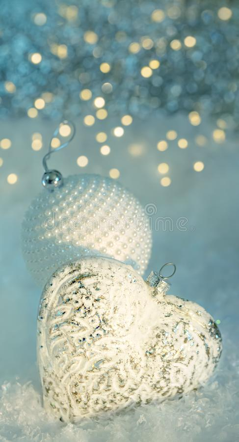 A glass heart and a white ball with pearls on a snow. Happy Merry Christmas and New year greeting postcard. Game of color. stock images