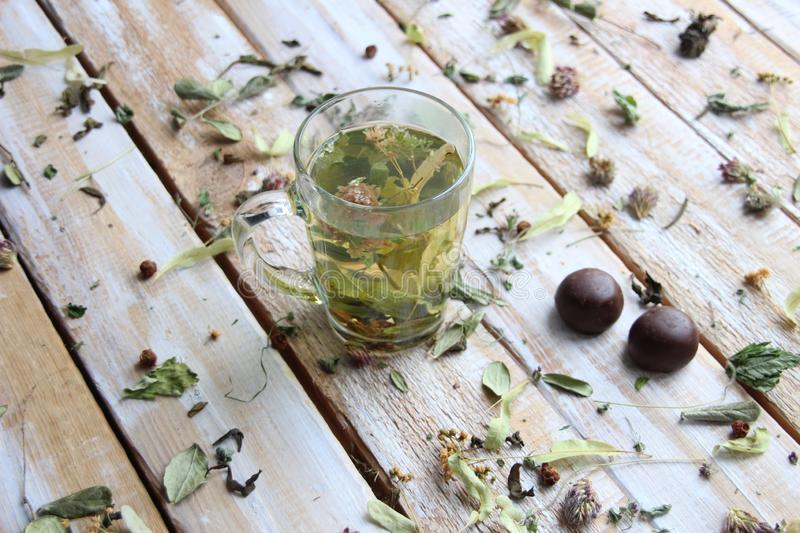Glass with herbal tea on wooden background with dry herbs an chocolate sweets stock photography