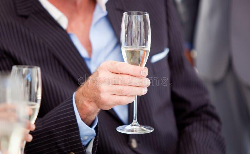 glass holding för affärsmanchampagne royaltyfri fotografi