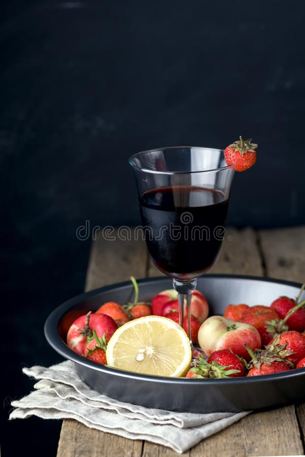 Glass of Homemade Fruit Berry Red Wine and Fresh Fruits on Tray Wooden Background Vertical stock photography