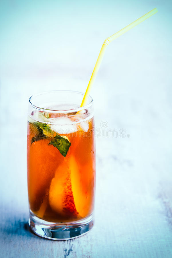 A glass with homemade ice tea, peach flavored. Freshly cut peach slices for arrangement. Light blue wood background. background. stock photo