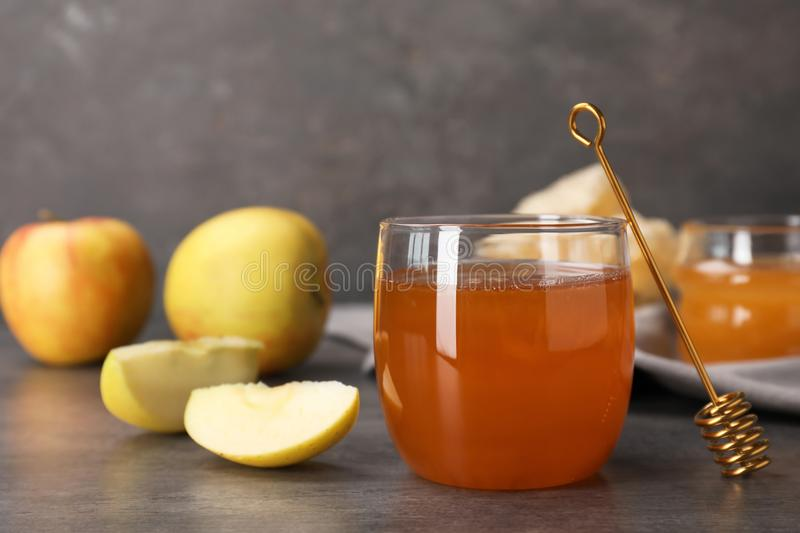 Glass of honey, apples and dipper. On dark table royalty free stock image