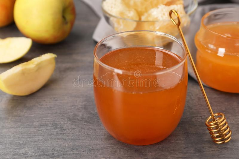 Glass of honey, apples and dipper. On dark table stock images