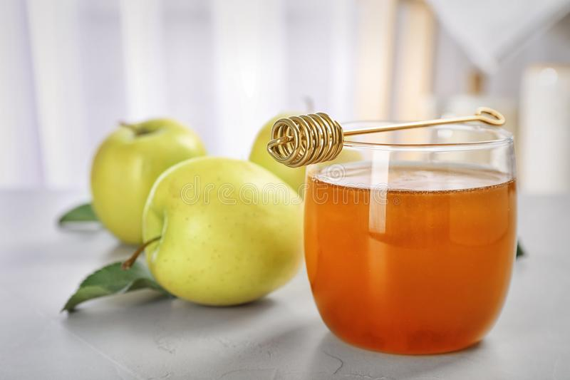 Glass of honey, apples and dipper. On light table royalty free stock image