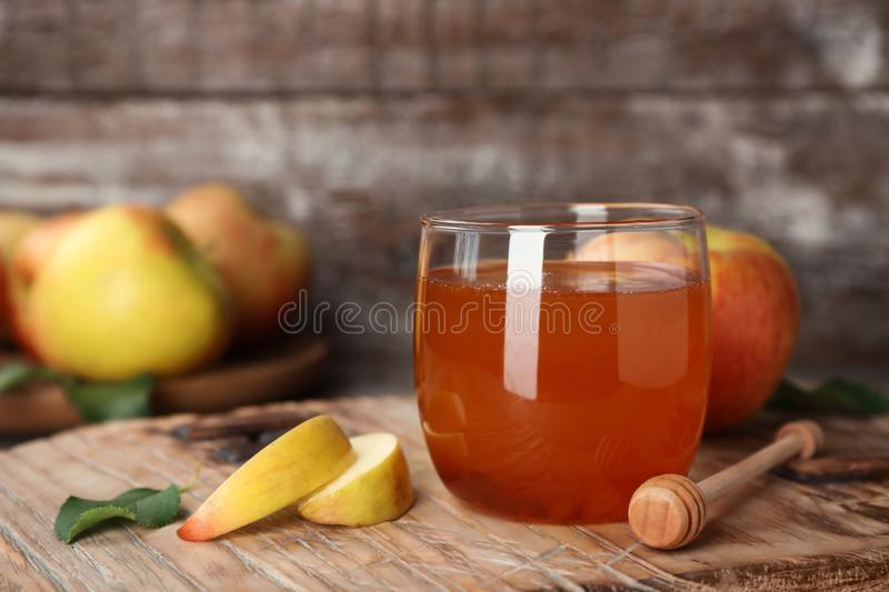 Glass of honey, apples and dipper. On wooden table stock photos
