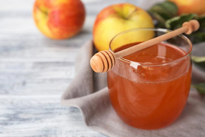 Glass of honey, apples and dipper. On wooden table royalty free stock photos