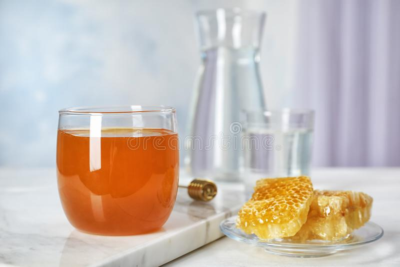Glass of honey and honeycombs. On table stock photo