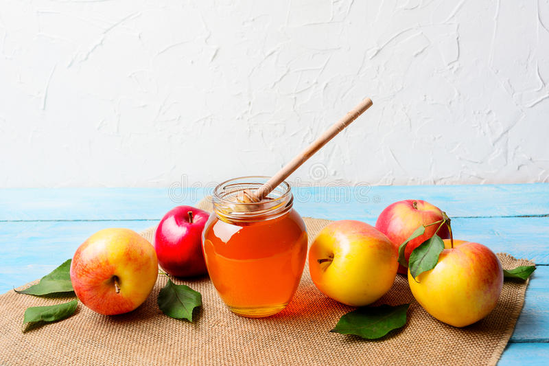 Glass honey jar with dipper and apples copy space royalty free stock image