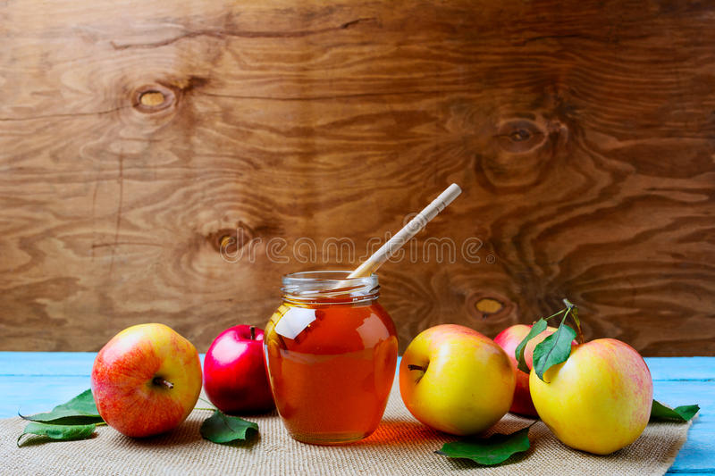 Glass honey jar with dipper and fresh apples, copy space royalty free stock photos