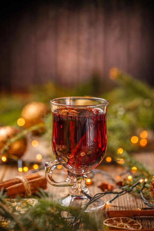 Glass with hot red wine. And spices on Christmas background stock photo
