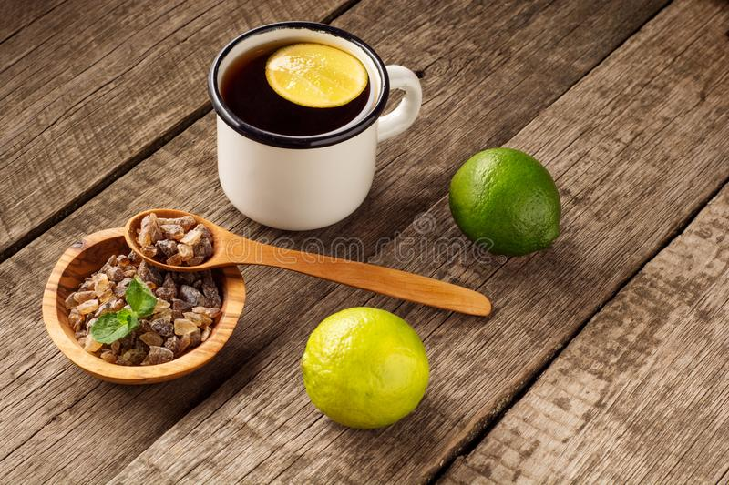 Glass of hot tea with lime, lemon, mint and brown sugar on old wooden table. Dark rustic style. stock images
