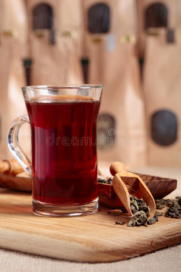 Glass of hot tea and wooden spoon with dried tea leaves. Glass of hot tea. Wooden spoon with dried tea leaves. Craft paper pack with window for loose tea stock photography