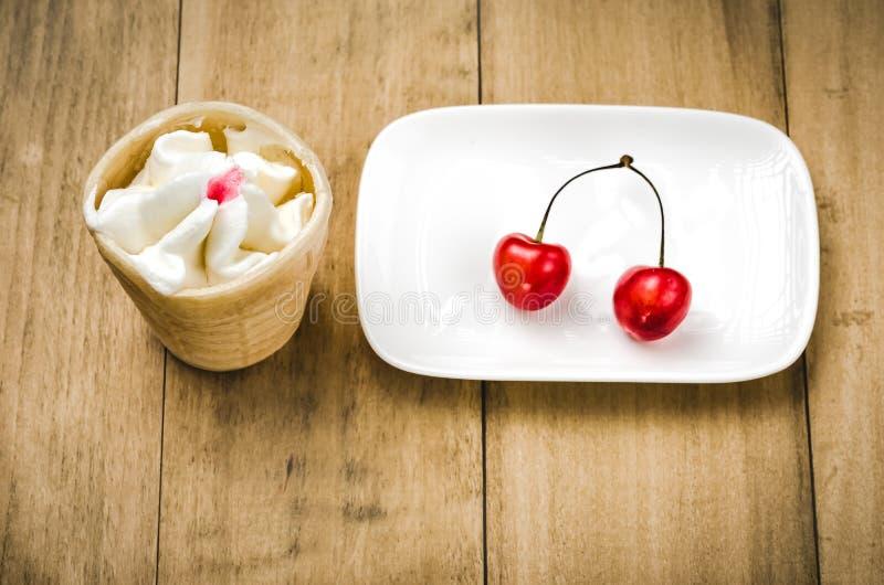 Glass i ett exponeringsglas med körsbäret i en vit platta/glass i ett exponeringsglas med körsbäret i en vit platta Top beskådar fotografering för bildbyråer