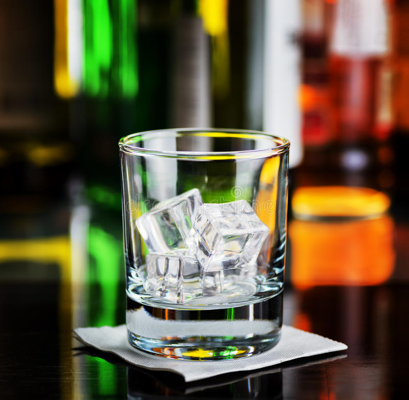 Glass with ice cubes on a bar desk royalty free stock photography