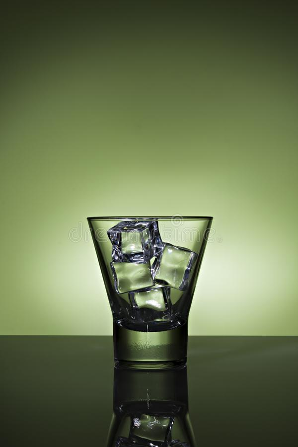 Glass with ice cubes on green background royalty free stock photos