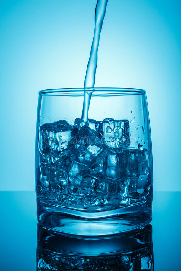 A glass with ice, dynamic splash jet. Drinking water. pour water into a glass, symbolic photo for drinking water, excess and waste royalty free stock photo