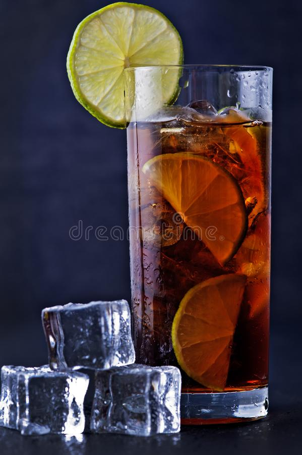 A glass of ice tea with lime. On a dark background stock image