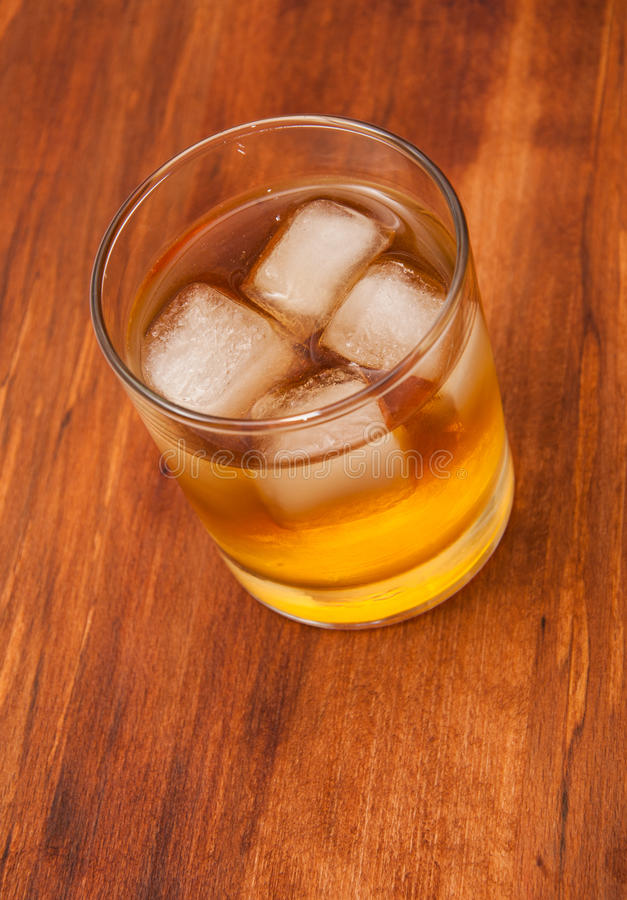 Glass with ice and whisky. Glass of whisky with ice peaces royalty free stock photography