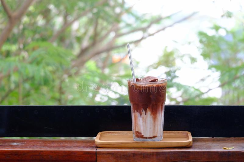 A glass of iced chocolate soft drinks with a steel straw in a wooden tray with an orange flower on wood balcony stock photography