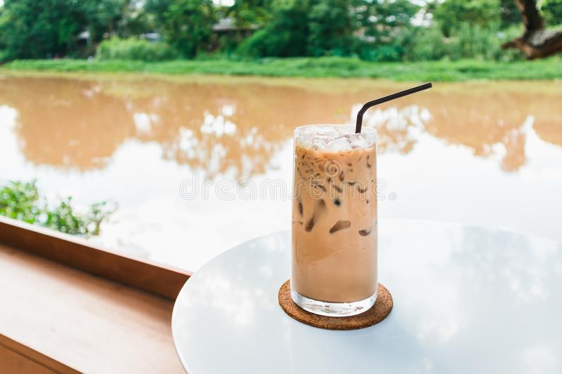 Glass of iced coffee by the riverside greenery background stock photo