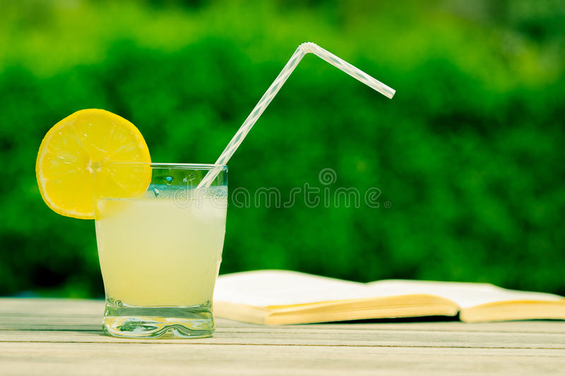 Iced lemonade and book on the table royalty free stock image