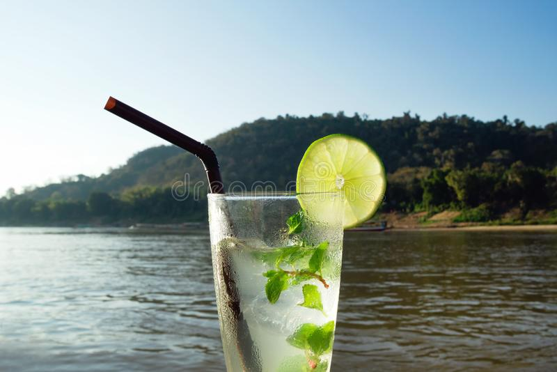 A glass of iced mojito with lime and leaves of mint on a background of river during of sunset. royalty free stock photography