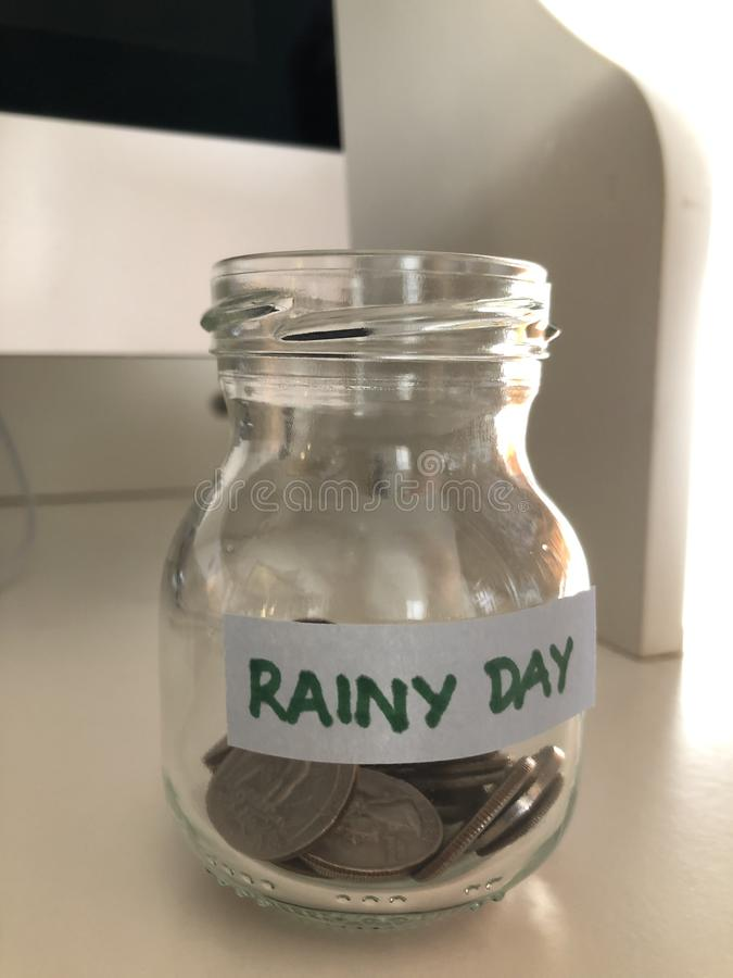 Creative concept, Saving for a rainy day. Glass jam jar labelled with the words Rainy Day, partially filled with coins, on a modern white desk stock images