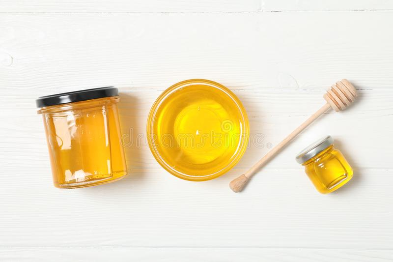 Glass jar and bowl with honey, dipper on white wooden background royalty free stock image
