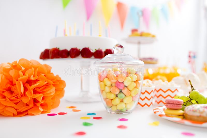 Glass jar with candy drops at birthday party. Food, confectionery and sweets concept - glass jar with colorful candy drops at birthday party stock image