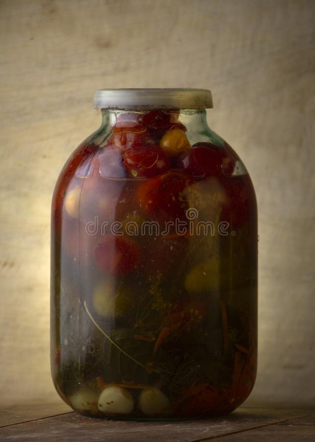 Glass jar of canned tomatoes on a wooden shelf in the cellar. Close up stock photo