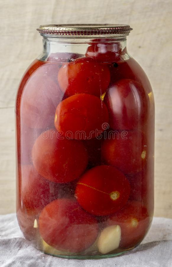 Glass jar of canned tomatoes on a wooden shelf in the cellar. Close up stock images