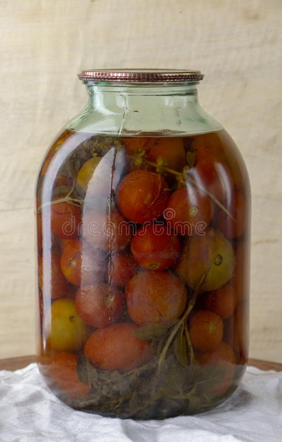 Glass jar of canned tomatoes on a wooden shelf in the cellar. Close up stock photos