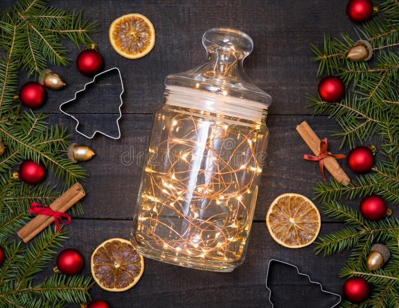 Glass jar with Christmas lights on dark wooden rustic background royalty free stock photography