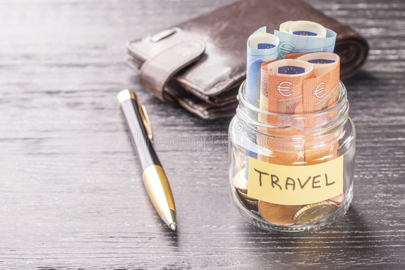 Glass jar with coins and euro notes with the word TRAVEL on a black wooden table. Leather wallet and pen royalty free stock photos