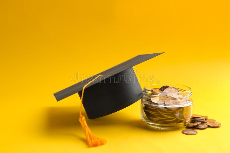 Glass jar, coins and graduation hat on color background. Space for text royalty free stock photo