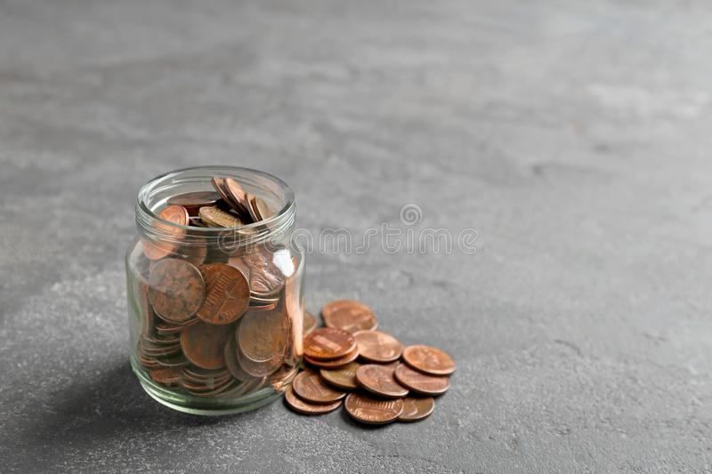 Glass jar and coins on grey table. Space for text stock photos