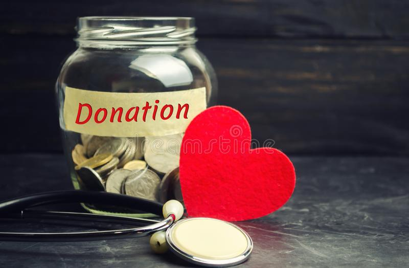 Glass jar with coins, heart and stethoscope and the inscription `Donation`. Medicine concept. blood transfusion, health care. Volu. Ntary blood surrender. organ royalty free stock photos