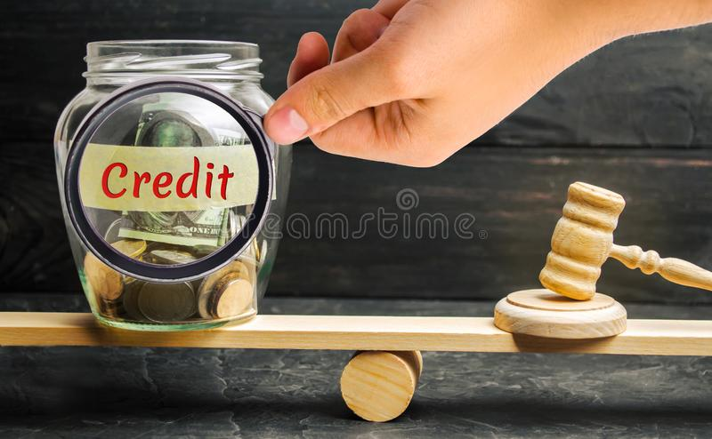 A glass jar with coins and the inscription `Credit` and the judge`s hammer are on the scales. Debt restructuring. Revision of loa. N terms. Termination of the stock photos