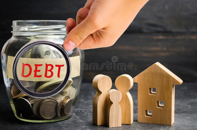 Glass jar with coins and the inscription ` Debt `, family and wooden house. Real estate, home savings, loans market concept. Payme stock photography