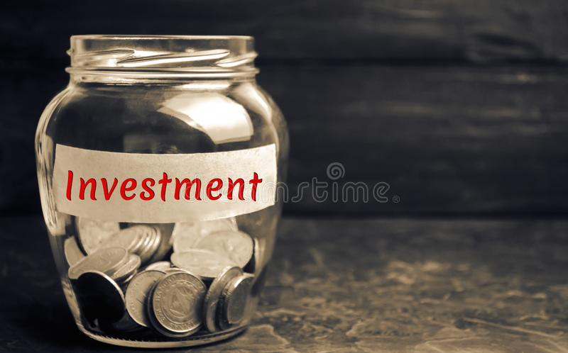 Glass jar with coins and the inscription ` Investment `. Investing in a new business project or real estate. Concept of economic f. Inancing. Saving money royalty free stock photo