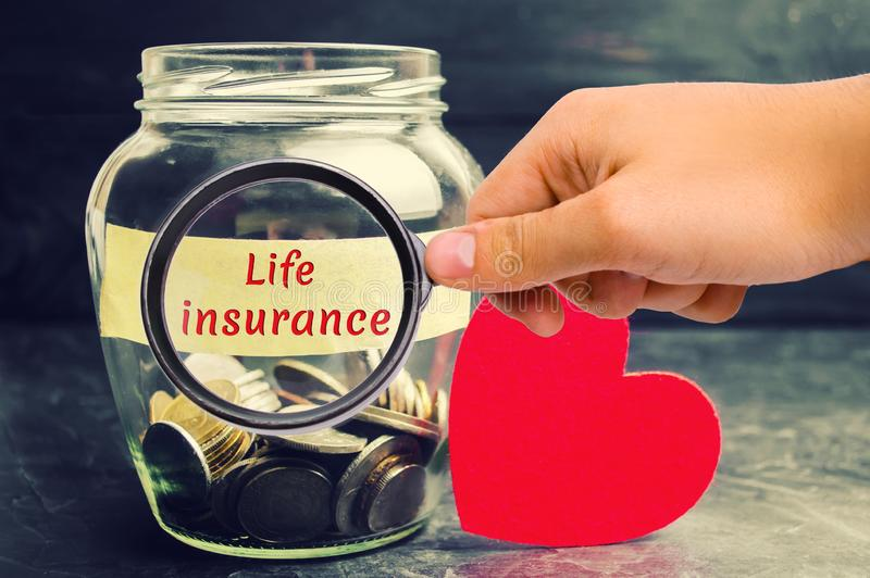 Glass jar with coins and the inscription `Life Insurance`. The concept of medical insurance of life, family, health. Healthcare. R stock photos