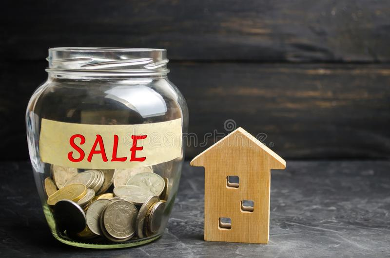 Glass jar with coins and the inscription `sale` and a small wooden house. real estate concept. sale of a home, apartment property. Sell. Affordable housing stock photos