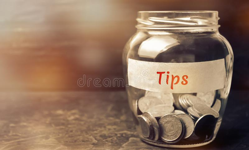 Glass jar with coins and the inscription ` Tips `. Award for good service in the cafe and restaurant. High level of service.  stock photos