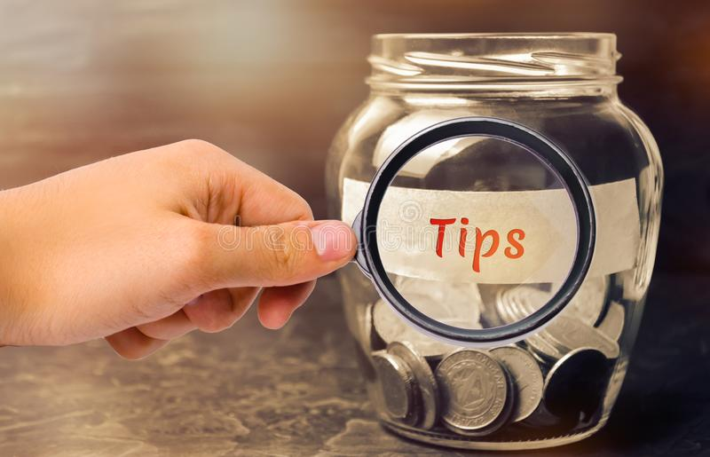 Glass jar with coins and the inscription ` Tips `. Award for good service in the cafe and restaurant. High level of service.  royalty free stock images