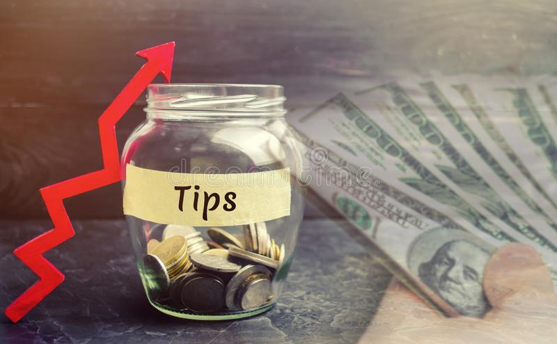 Glass jar with coins and the inscription ` Tips ` and up arrow. Award for good service in the cafe and restaurant. High level of s royalty free stock photography
