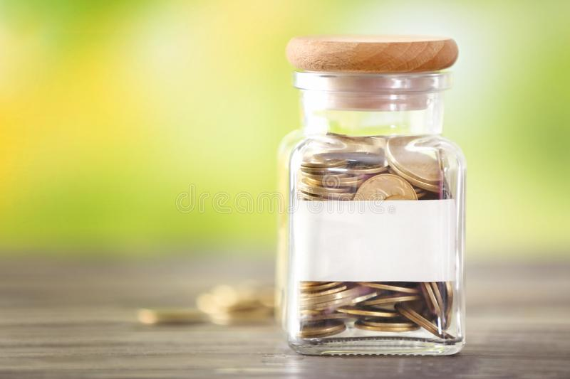 Glass jar with coins and label on table against blurred background. Concept of savings stock images