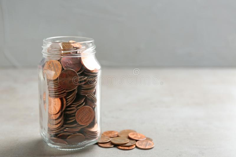 Glass jar and coins on table. Space for text. Glass jar and coins on table against grey background. Space for text royalty free stock photo