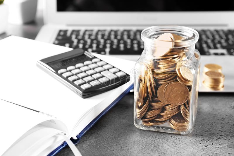 Glass jar with coins on table. Concept of savings royalty free stock image