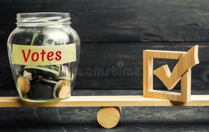 Glass jar with coins and the words `Votes` and a checkbox on the scales. Concept of voting for money. Bribing voters. Corruption i royalty free stock image