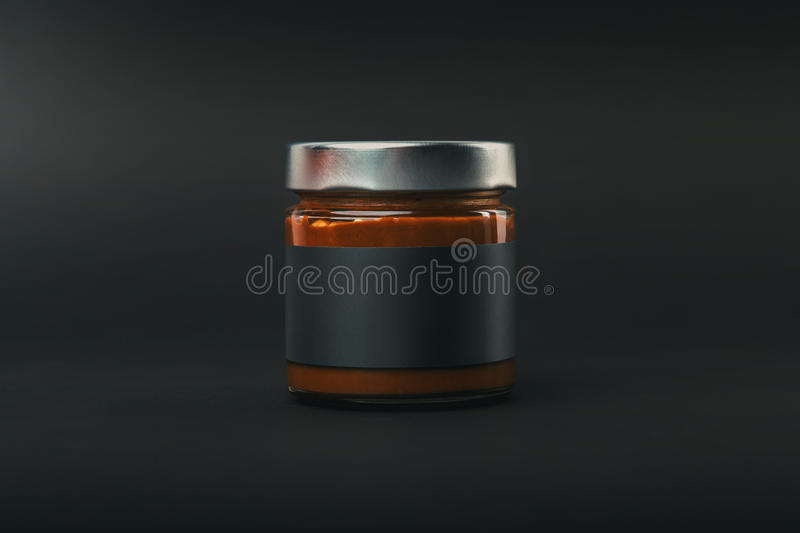 Glass jar. With the contents, closed the metal lid. With blank white sticker. On a black background stock photo
